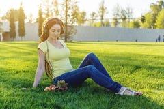 Härlig modern flicka som lyssnar till musik med hennes hörlurar i hösten Sunny Park Favorit- musik, lycklig tid fotografering för bildbyråer