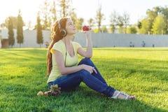 Härlig modern flicka som lyssnar till musik med hennes hörlurar i hösten Sunny Park Favorit- musik, lycklig tid royaltyfri bild