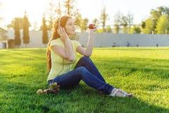 Härlig modern flicka som lyssnar till musik med hennes hörlurar i hösten Sunny Park Favorit- musik, lycklig tid royaltyfri fotografi