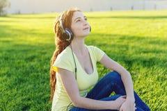 Härlig modern kvinna som lyssnar till musik med hennes hörlurar i hösten Sunny Park Bra lynne och favorit- musik royaltyfri foto