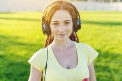 Härlig modern kvinna som lyssnar till musik med hennes hörlurar i hösten Sunny Park Bra lynne och favorit- musik royaltyfria foton