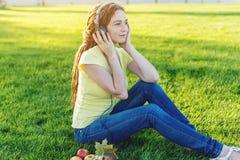 Härlig modern kvinna som lyssnar till musik med hennes hörlurar i hösten Sunny Park Bra lynne och favorit- musik arkivbild