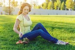 Härlig modern kvinna som lyssnar till musik med hennes hörlurar i hösten Sunny Park Bra lynne och favorit- musik arkivbilder