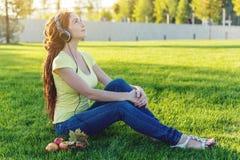 Härlig modern kvinna som lyssnar till musik med hennes hörlurar i hösten Sunny Park Bra lynne och favorit- musik arkivfoto