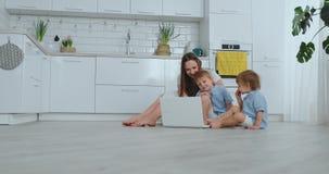 Härlig modern ung familj som hemma ligger på golvet och gör något i bärbar dator stock video