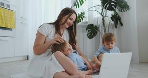 Härlig modern ung familj som hemma ligger på golvet och gör något i bärbar dator lager videofilmer