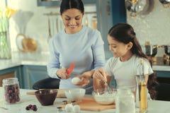 Härlig moderundervisningdotter hur man bryter ägg fotografering för bildbyråer