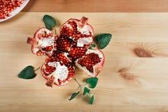 Härlig mogen granatäpple som ligger på träbakgrunden Arkivfoto