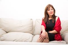 Härlig mogen kvinna på soffan hemma Arkivfoto