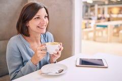 Härlig mogen kvinna som ler, medan rymma hennes kaffe på tabellen Arkivfoton