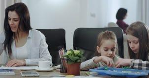 Härlig mogen moder som gör läxa med deras ungar i ett modernt hus som koncentreras mycket dem som tillsammans spenderar tid lager videofilmer