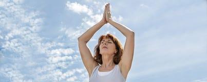 Härlig mogen yogakvinna som övar, i att be position utomhus, baner Royaltyfria Foton