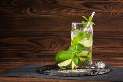 Härlig mojitococtail med ett sugrör, en mintkaramell, iskuber och skivor av limefrukt på träbakgrunden kopiera avstånd Royaltyfria Bilder