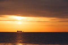 härlig molnig gryning vaggar havsskyvatten I avståndet kan ett skepp ses Royaltyfria Bilder