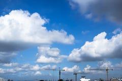 Härlig molnig skyscape av staden med byggnader och kranar Arkivbilder