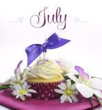 Härlig muffin för lila- och rosa färgsommartema med säsongsbetonade blommor och garneringar för månaden av Juli Arkivfoton