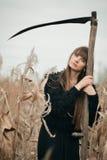 Härlig mystisk mystisk flicka med långt hår i den svarta klänningen som rymmer en flätad tråd i mörk höstskog på vägen Mystiskt n Arkivbild