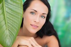 Härlig näck brunett som ler på kameran med det gröna bladet Royaltyfria Foton