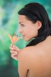 Härlig näck brunett som luktar liljan Fotografering för Bildbyråer