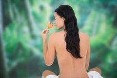 Härlig näck brunett som luktar liljan Royaltyfri Foto