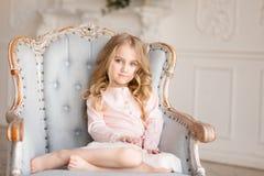Härlig nätt flicka med blåa ögon som sitter i fåtölj som ler Inomhus foto royaltyfri foto