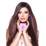 Härlig nätt kvinna med den långa hår- och rosa färgrosen på framsidan Royaltyfri Fotografi