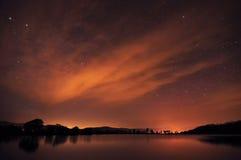Härlig natthimmel med stjärnor, moln och reflexioner i waen Arkivfoton
