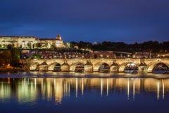 Härlig nattsikt vid vattnet med folk på upplysta Charles Bridge och Prague royaltyfria bilder