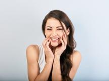 Härlig naturlig toothy skratta kvinna med stängda ögon som rymmer huvudet i den vita skjortan med den långa lockiga frisyren clos arkivbild