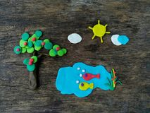 Härlig naturplasticinelera, damm för fisk för sol för moln för äppleträd, träbakgrund arkivfoto