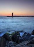Härlig nightly seascape med fyren och lynnig himmel på arkivfoton