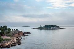 Härlig nordisk skärgårdsommarsikt av land och ön mot havet och disig horisont royaltyfri foto
