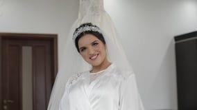 Härlig och älskvärd brud i nattkappa och att skyla bröllop för klänningfragmentbeställning långsam rörelse stock video