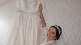 Härlig och älskvärd brud i nattkappa och att skyla bröllop för klänningfragmentbeställning långsam rörelse lager videofilmer