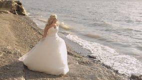 Härlig och älskvärd brud som promenerar kusten av havet Nätt och brunn-ansad kvinna blont hår soligt väder bröllop stock video