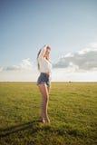 Härlig och attraktiv kvinna med sexiga ben på grässkon som håller ögonen på mindre solen med hennes hand ovanför henne ögon royaltyfria bilder