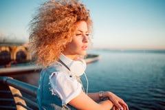 Härlig och gladlynt ung kvinna med frodigt hår, utomhus royaltyfri fotografi