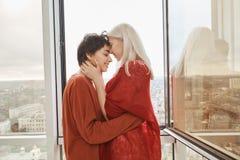 Härlig och gullig kvinnlig i förhållandet som kysser och kelar nära öppet fönster, medan stå på balkong flickvänner Fotografering för Bildbyråer