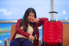 Härlig och lycklig asiatisk koreansk turist- kvinna med loppresväskan i flygplatssammanträde på avvikelser som väntar på flyg som royaltyfri foto