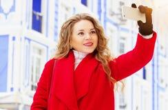 Härlig och stilfull för blont hår flicka för barn, i det röda laget som tar en selfie på hennes telefon Kvinnors mode Royaltyfri Foto