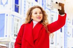 Härlig och stilfull för blont hår flicka för barn, i det röda laget som tar en selfie på hennes telefon Kvinnors mode Arkivbilder