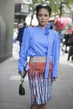 Härlig och stilfull kvinna i blå blus och blåttkjolen som poserar under den London modeveckan utvändiga Eudon Choi Royaltyfri Foto