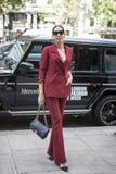 Härlig och stilfull kvinna i den burgundy dräkten som poserar mot en Mercedes bakgrund under den London modeveckan utvändiga Eudo Arkivbild