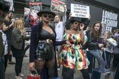 Härlig och stilfull kvinna som poserar under den London modeveckan Anti-pälsprotest som en bakgrund Arkivfoto