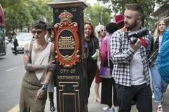 Härlig och stilfull ung man för A med tatueringar och en kaki- overall som poserar under den London modeveckan utvändiga Eudon Ch Arkivfoton