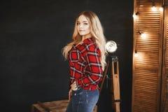 Härlig och trendig blond pluss-format modellflicka med det stora bröstet i röd plädskjorta och i jeans, ställningar nära träcet royaltyfri bild
