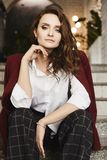 Härlig och trendig brunettmodellflicka med perfekt smink, i ett stilfullt rött omslag och i moderiktigt rutigt royaltyfri bild