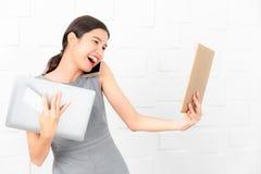 Härlig och ung asiatisk kvinna som ler händer som rymmer minnestavlan och arkivbild