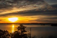Härlig orange guld- vinterlandskapsolnedgång mot vatten och horisont arkivbilder