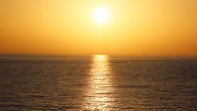 Härlig orange solnedgång med havet i rörelse på sommartidcloseupen Grekland arkivfilmer